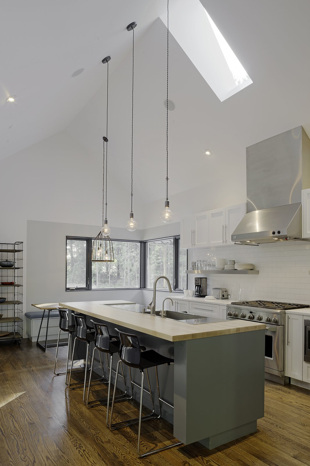 """""""Knowing that the kitchen would be where the family would spend most of their time, it was designed to have a variety of seating and really good views to the beautiful forest and field outside,"""" says Lewis. IKEA bar stools line up against white quartz countertops, and lighting by Schoolhouse Electric & Supply Co. shines overhead.  The Farmhouse by Kelly Dawson"""