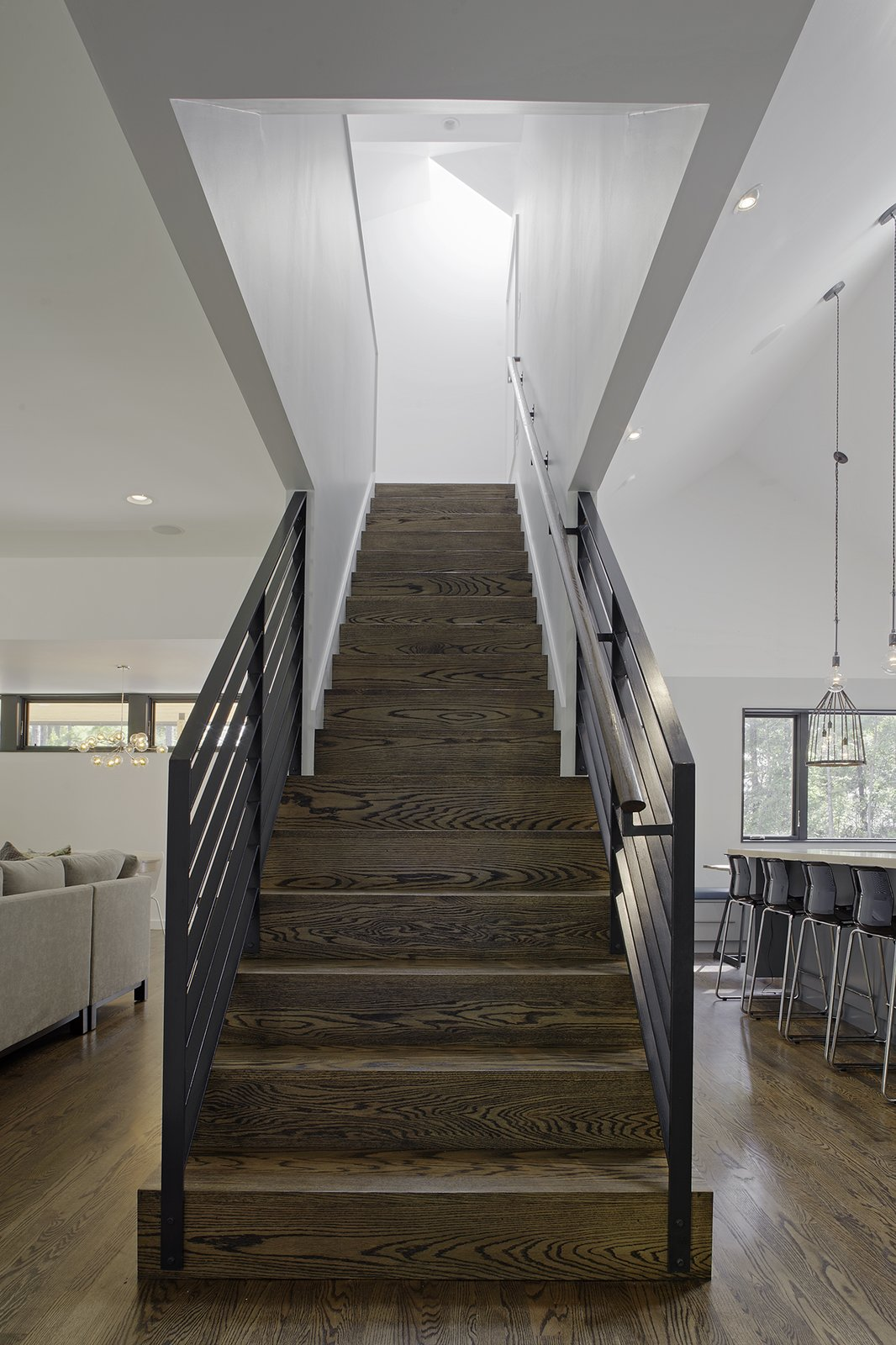 Stained oak flooring was used throughout the home's ground level, and continues up the main stairwell. Painted steel was used for the guardrails.  190+ Best Modern Staircase Ideas by Dwell from The Farmhouse