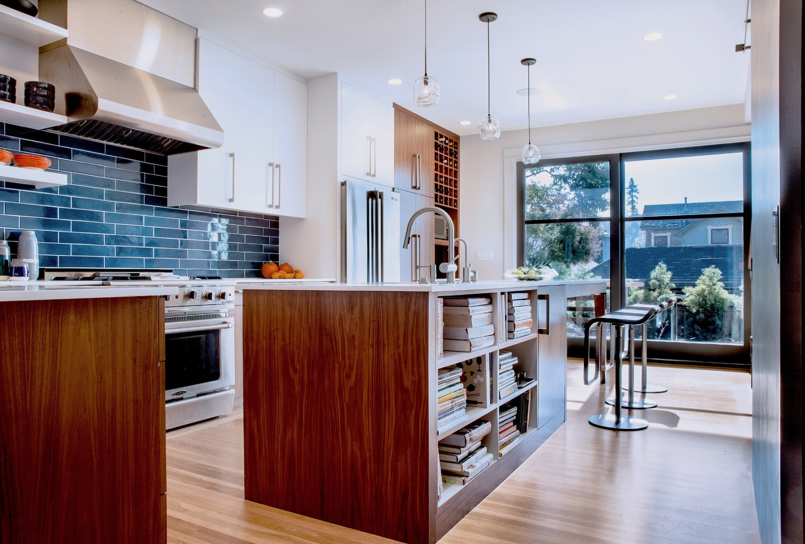 A first priority for the kitchen was sunlight: to maximize exposure, Mitchell Holladay Architects demolished as many walls as possible without compromising the home's structural integrity. LEM Piston stools by Shin and Tomoko Azumi from Design Within Reach flank a custom walnut kitchen island; sculptural hand-blown glass pendants from John Pomp Studios hang overhead.  Renovated Kitchens We Love by Zachary Edelson from A Fresh Kitchen Update for the Family That Cooks Together