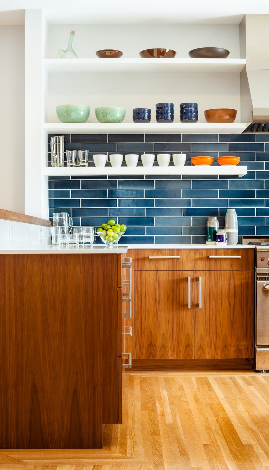 The residents have a particularly strong sense of color and love to cook with their son, so no-fuss finishes likes these blue tiles from Heath Ceramics were an ideal choice. The tiles combine with colorful tableware and custom walnut cabinetry to make a vibrant inteiror.  Photo 16 of 21 in The Pantone Choice: Top 10 Colors for Spring 2017 from A Fresh Kitchen Update for the Family That Cooks Together