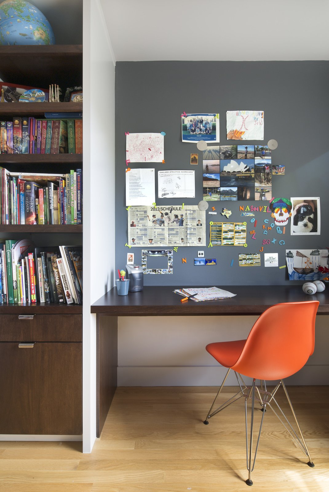 Upstairs, their son's bedroom features a built-in walnut bookshelf and desk. Smart details—like the magnetic paint in lieu of a bulletin board—help keep the space tidy. The chair is an Eames Molded Fiberglass Side Chair.  Photo 6 of 11 in 10 Essential Tips For Creating a Hardworking Home Office from A Fresh Kitchen Update for the Family That Cooks Together
