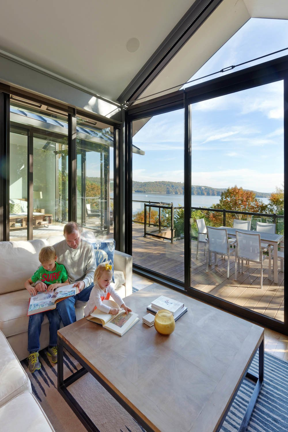 The living room and a deck offer expansive views of Table Rock Lake.  Photo 6 of 9 in Modern Lake House in Missouri