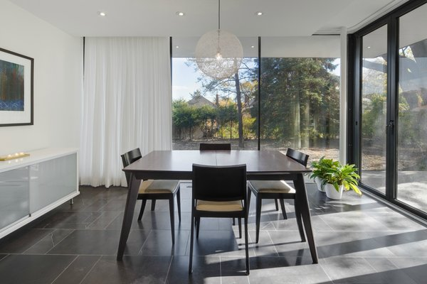 A table and accompanying chairs by EQ3 sit under a Moooi light fixture in the dining room, a room that was added to the original structure. Glass doors from NanaWall allow for the patio and dining area to become one cohesive space in the warmer months. Photo 3 of Art Moderne modern home