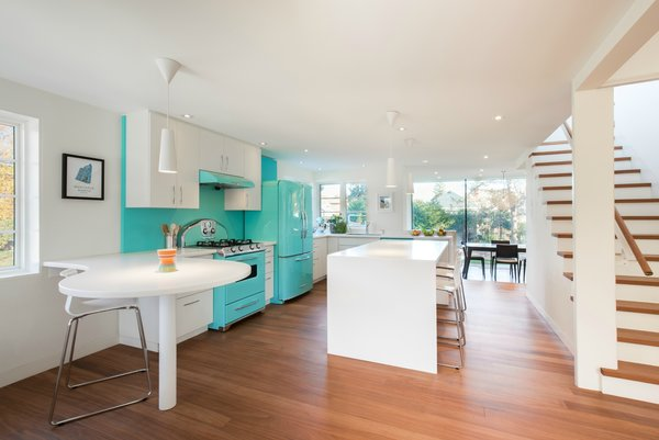 Modern home with kitchen and white cabinet. The owners brought their Elmira Stove Works appliances, including the Model 1958/1959 refrigerator and the matching Model 1955 stove, into their new home. Custom cabinets and IKEA chairs provide an equally bright finish. Photo 4 of Art Moderne