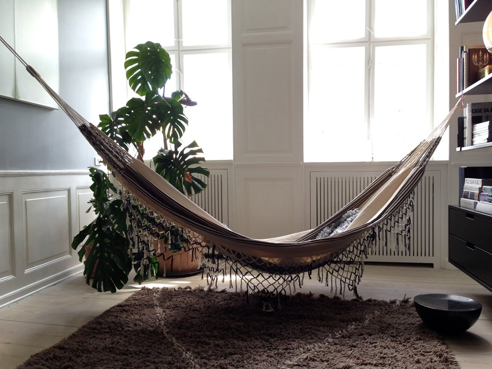 The color palette may be restrained, and the price tags high, but it's not all serious: Check out the hammock hung in the office between the living room and bedroom.