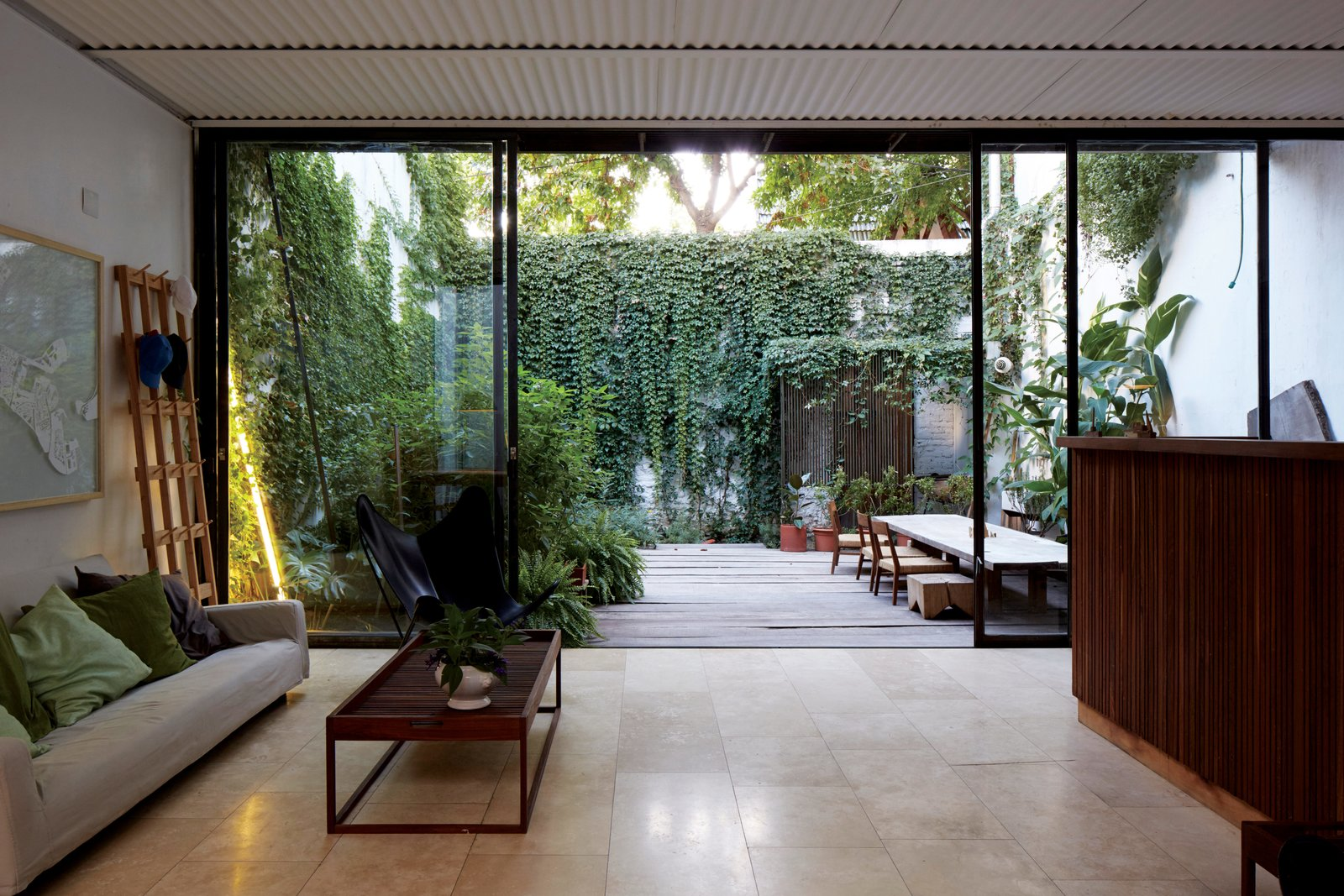 """The main living area is flanked by green spaces, with custom sliding doors made from materials sourced from a metal warehouse. The ceiling is corrugated sheet metal, a """"common and cheap but noble"""" construction material, Teresa says. One-of-a-Kind Furniture Fills This Delightfully Serene Buenos Aires Home - Photo 4 of 10"""
