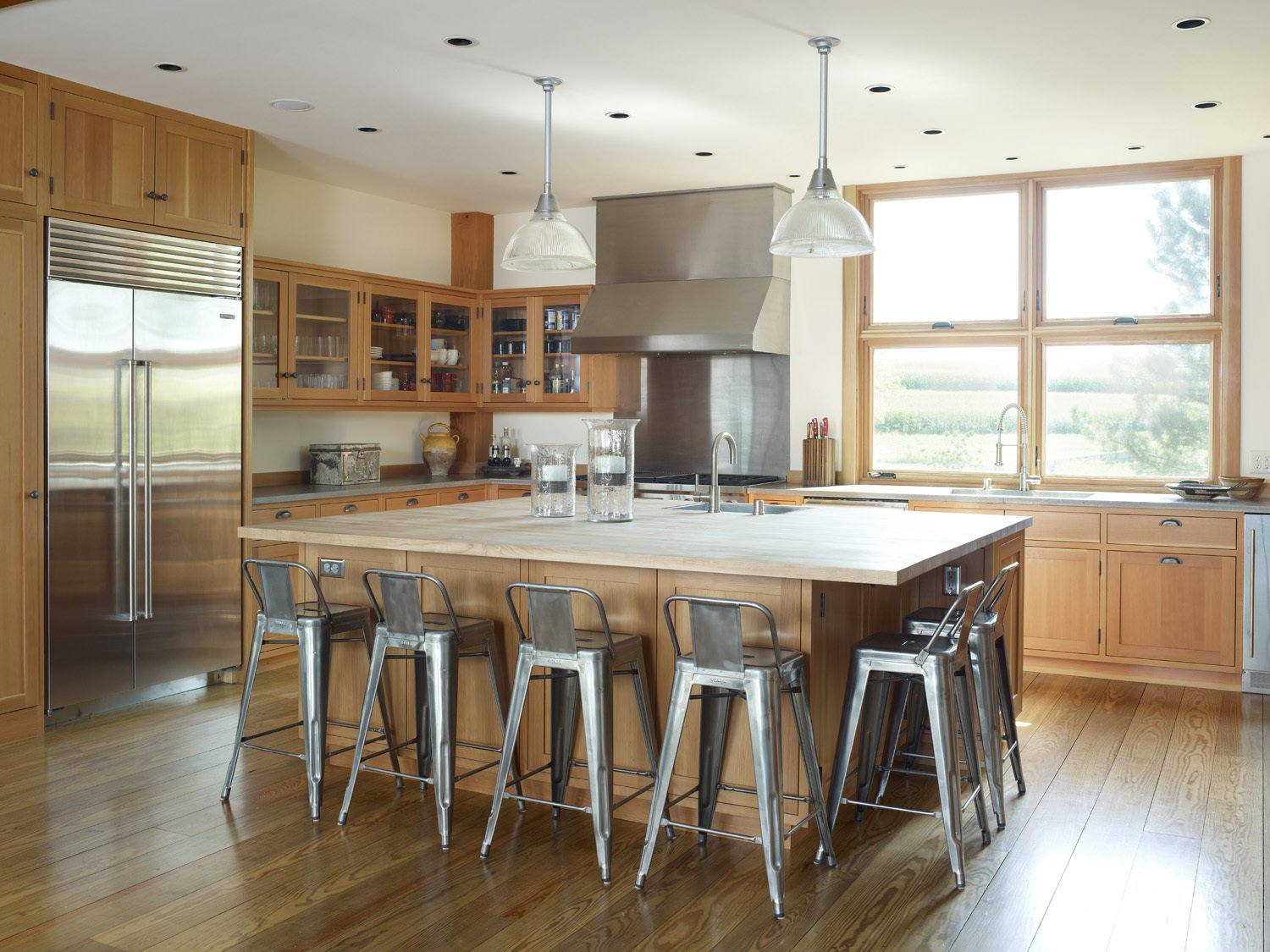 The homeowners needed a kitchen that could hold the 20 or so friends and family members they usually host on holidays and reunions. The kitchen island—which features a countertop of recycled paper and cement from Squak Mountain Stone—can easily accommodate plenty of Tolix aluminum bar stools. Custom Douglas fir cabinetry frames a Miele dishwasher, Sub Zero refrigerator, Blanco sink, and a Wolf oven with a Vent-A-Hood overhead.