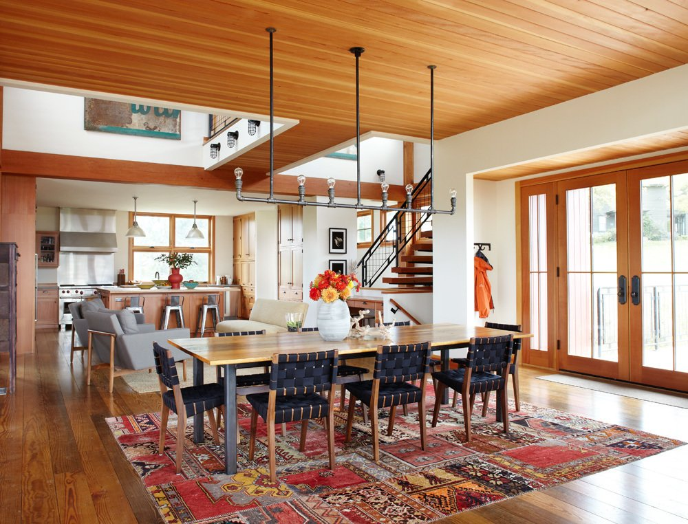 The aluminum pipe light fixture and white oak dining room table—made from the original barn's horse stalls—were both DIY projects completed by one of the homeowners and their friend, respectively. A design from The Rug Company, made from patches of old rugs, sits under the table.
