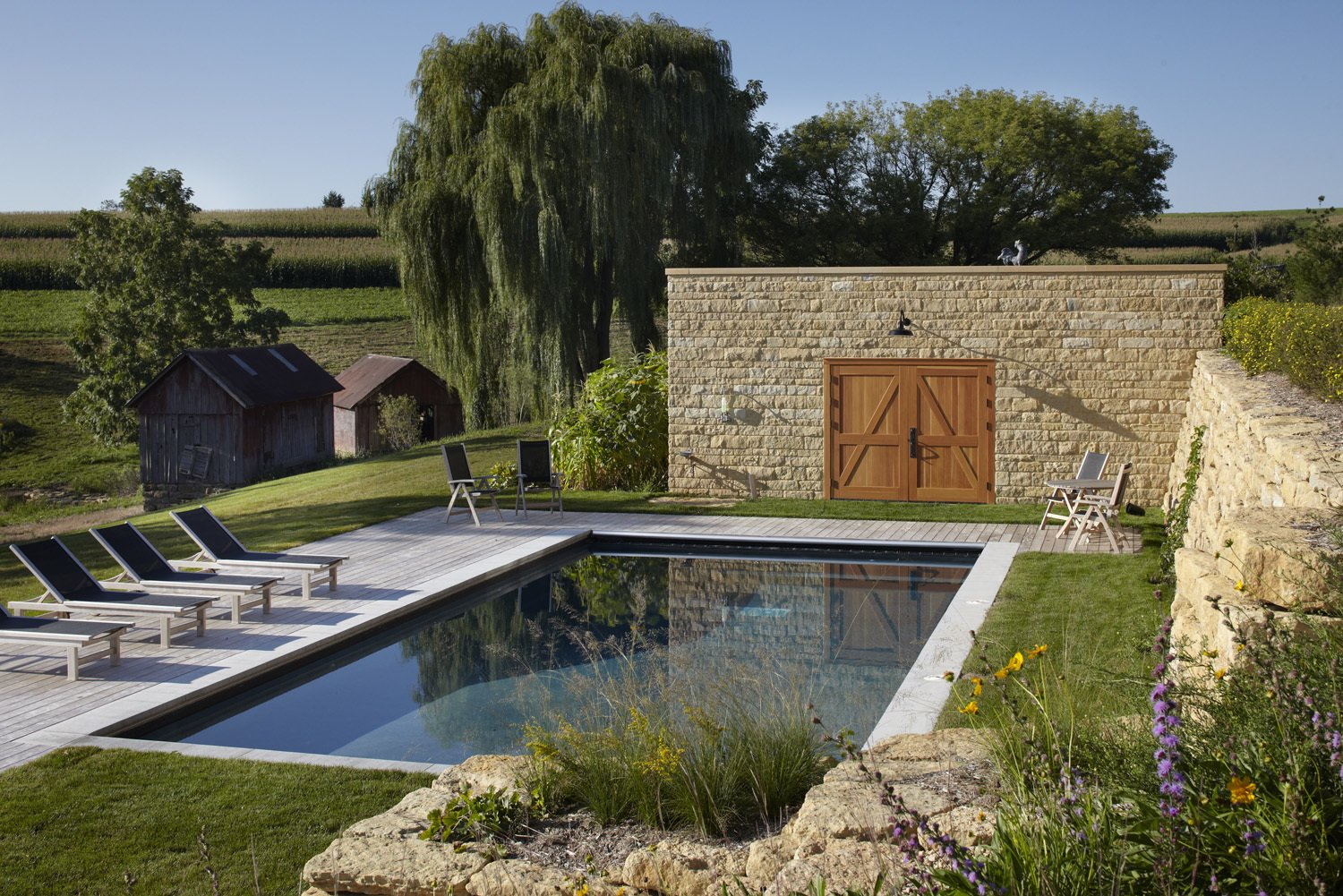 The old barn's foundation, re-stacked by a local stonemason, was reused as a rustic retaining wall for the pool area. The property also came with a corn crib and blacksmith shop as old as the barn, seen behind the pool, which are both used for storage now. St. Tropez chaises from Kingsley-Bate line the pool. Tagged: Outdoor, Wood Patio, Porch, Deck, Large Patio, Porch, Deck, Swimming Pools, Tubs, Shower, Large Pools, Tubs, Shower, and Concrete Pools, Tubs, Shower.  A Family Salvages an 1880s Barn to Create Their Nearly-Net Zero Escape by Caroline Wallis