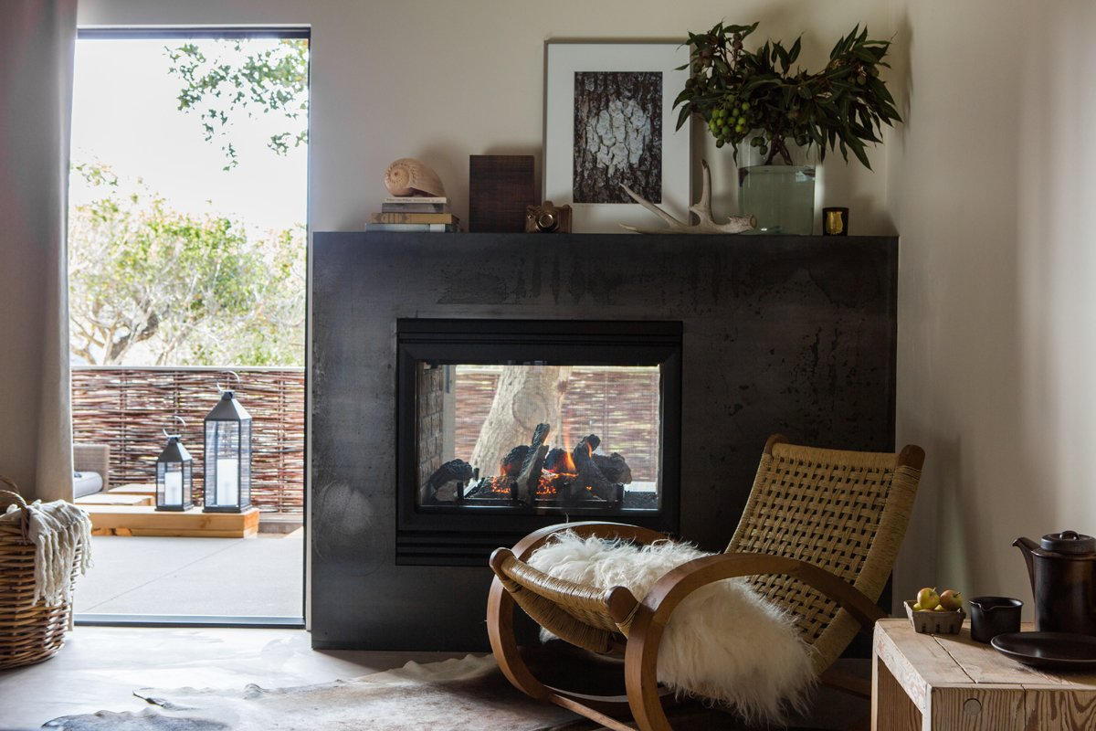 The double-sided fireplace is wrapped in a custom surround made fron Cor-Ten steel. The rocker is vintage and the artwork is from the Lost Art Salon.  97+ Modern Fireplace Ideas by Dwell from A Serene Hotel in Carmel, California