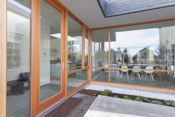"""The front exterior entryway features expansive windows and door by Quantum, which lead into the dining and living area of the main floor. """"[Pulling] as much natural light into the interior as possible"""" was one of the clients' biggest requests, says architect Mike Mora of Heliotrope. Photo 2 of Central District Residence modern home"""
