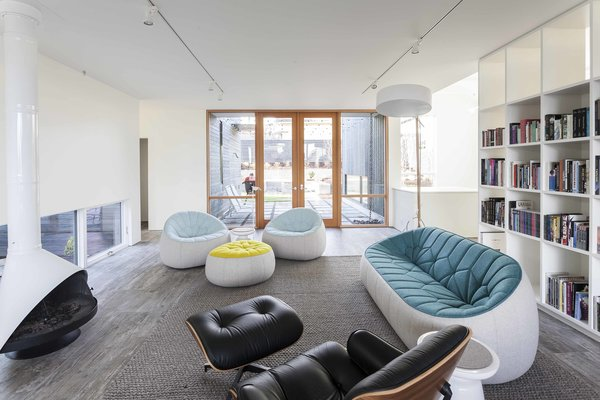 The main living area is one of the owners' favorite aspects of the home. A Malm fireplace, Eames lounge chair and ottoman, and Roll & Hill Excel floor lamp are sleek statement pieces, while the Ligne Roset Ottoman Series chairs add fun pops of color. The rug is from Design Within Reach.