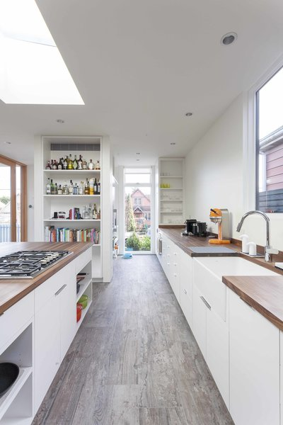The kitchen, framed by Loewen windows, features walnut butcher block countertops, custom made by Dovetail, a Hansgrohe faucet, Franke apron sink, Miele refrigerator and oven, and Thermador cooktop. Photo 5 of Central District Residence modern home