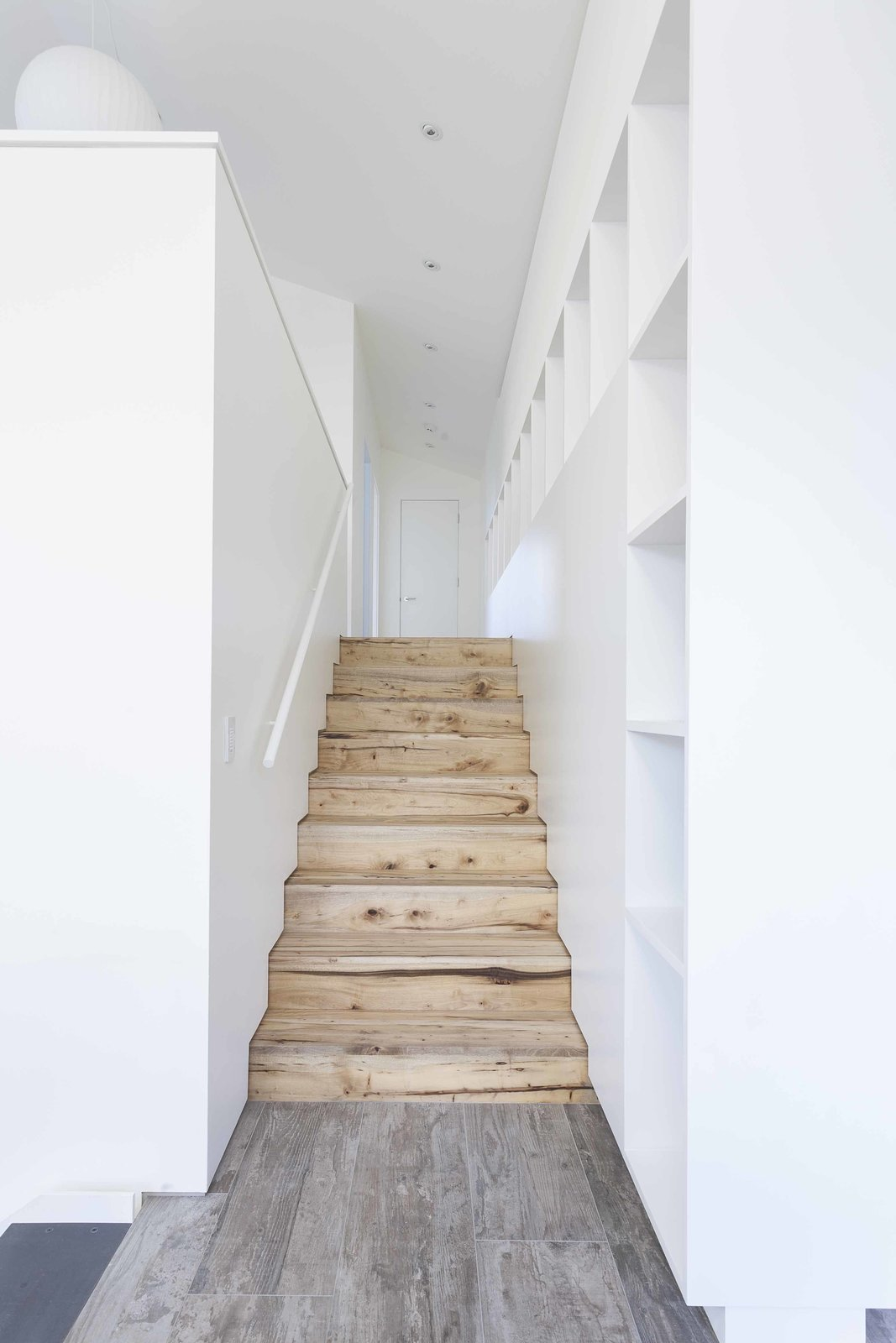 "Executing subtle design details, even in transitional spaces, was one of the great successes of the collaborative architect-contractor relationship. ""Our collective strength,"" says Dovetail principal Chad Rollins, is that ""we genuinely understand each other's craft."" In the transition from the den to the artist studio, natural myrtlewood stairs meet a wood-grain Daltile landing. Where the stair treads and risers meet the wall, a three-quarter-inch reveal is placed in lieu of conventional baseboard. These simple and clean details so often ""can be costly to create and can be jeopardized when the budget is under pressure,"" says Rollins."
