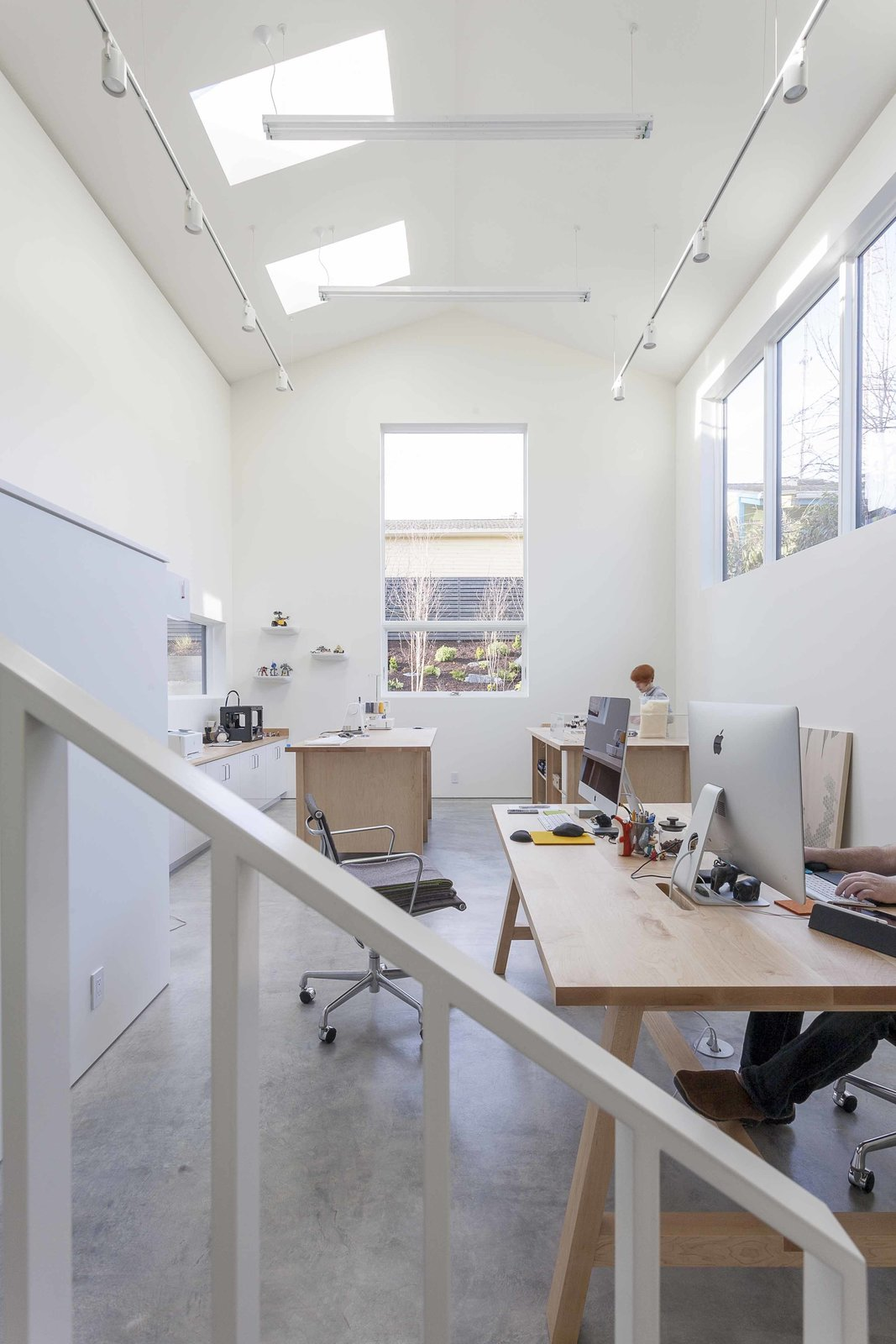 "The double-height artist studio showcases custom pieces by Dovetail, like a metal handrail and maple work tables, as well as Eames Aluminum Group chairs. The goal for the home, says Heliotrope principal Mike Mora, was to, ""Create an interior space akin to an art gallery with white wall surfaces adequate to hang art.""  Central District Residence by Sarah Akkoush"