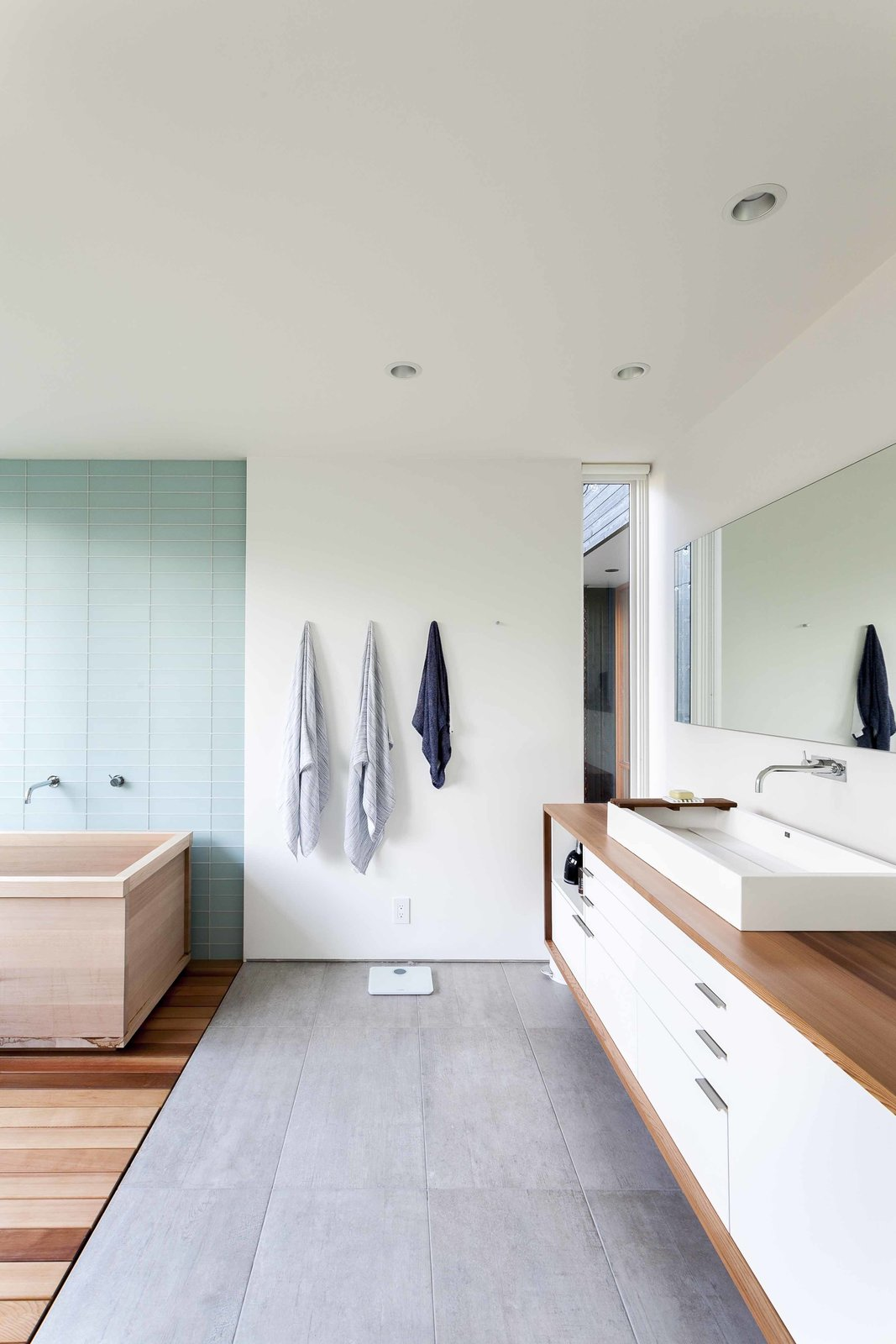 The owners were passionately involved in every aspect of the design, and pushed the team to make choices they normally might not have, including using Western red cedar for the master bathroom countertop. The spa-like space features a soaking tub, tile from Statements Urban, an MTI sink, a custom mirror, and a Vola faucet. Tagged: Bath Room, Vessel Sink, and Concrete Floor. Bath & Spa Intrigue - Photo 6 of 22