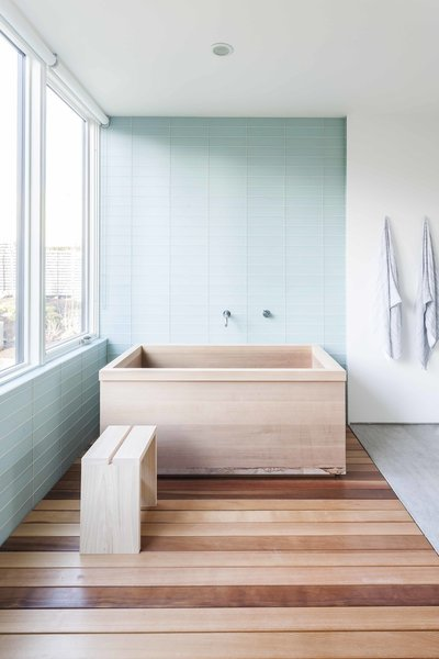 Modern home with bath room, freestanding tub, glass tile wall, and light hardwood floor. The custom cedar tub, fabricated by Dovetail, elegantly fits into the master bathroom. Photo 9 of Central District Residence