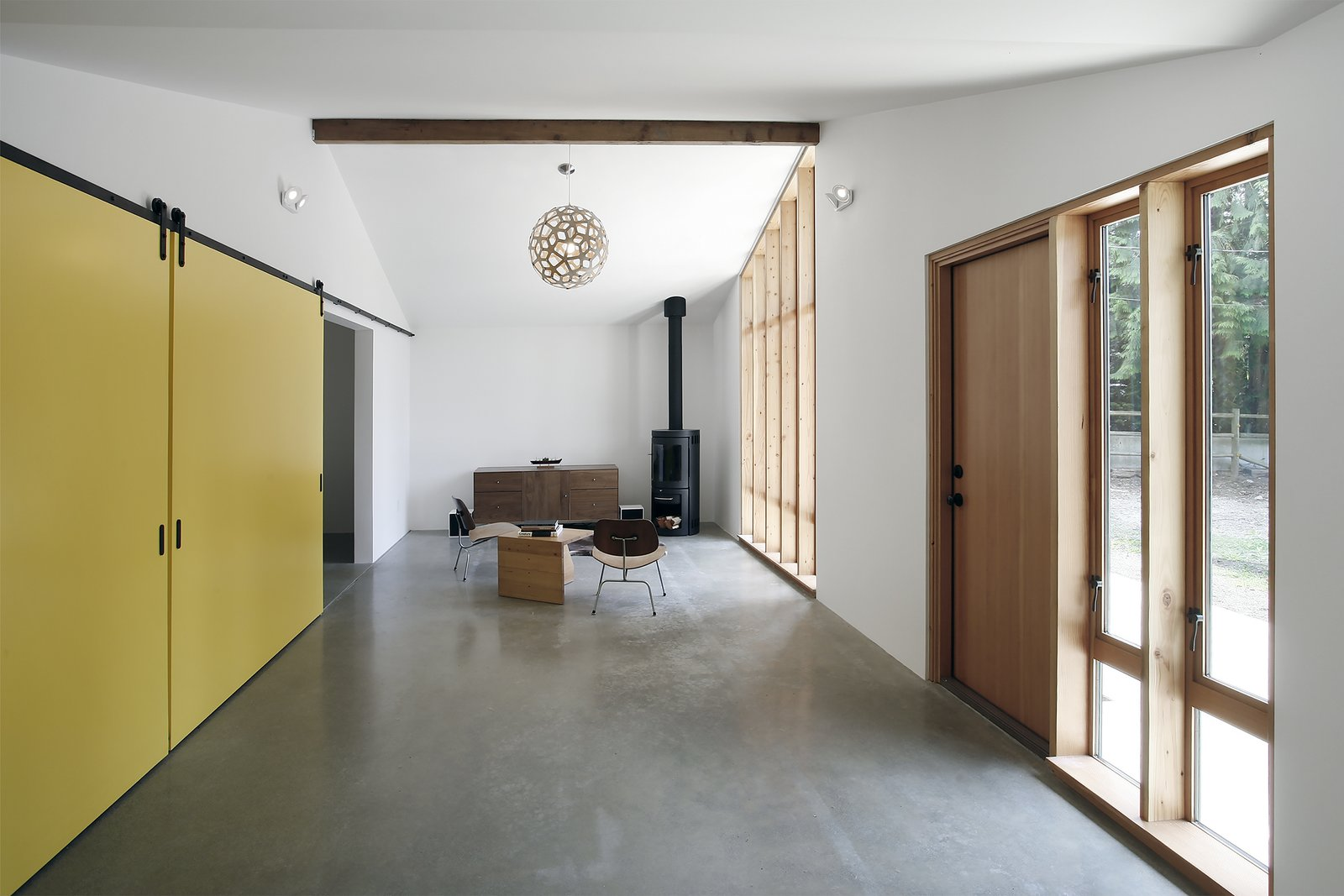 The renovated stable's living room is extra bright thanks to walls painted with Benjamin Moore's Atrium White and reflective polished concrete floors. The latter conceal a radiant heating system. Horse Stable Studio by Kelly Dawson