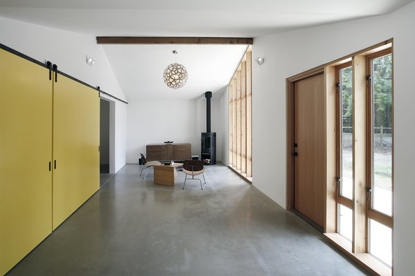 The renovated stable's living room is extra bright thanks to walls painted with Benjamin Moore's Atrium White and reflective polished concrete floors. The latter conceal a radiant heating system.
