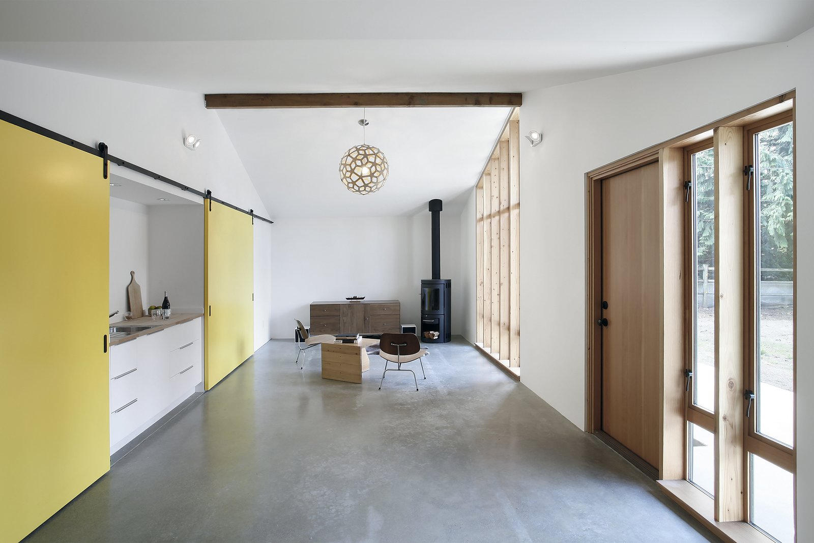 To evoke the structure's past as a horse stable, and provide options for the use of the space, Schaer and his team employed Sing Core sliding barn doors mounted on Krownlab's Axel hardware. The sliding track runs the full width of the building, allowing residents to open or conceal a bedroom, kitchenette, and entrance to an adjacent 530 square-foot garage, all depending on how the spaces are being used. The kitchenette, seen left, features a Kraus sink and a chrome Grohe Concetto faucet.  Horse Stable Studio by Kelly Dawson