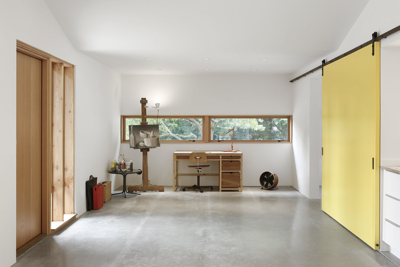 """""""Concrete floors, drywall, and minimal use of trim allowed for the feel of the space to remain utilitarian, while exposed Douglas fir structural members created a connection to regional Pacific Northwest design,"""" Schaer says. The clients wanted a place for painting and occasional freelance work, which fits opposite the room's fireplace and seating area. A Kevi Chair by Jørgen Rasmussen accompanies the desk."""