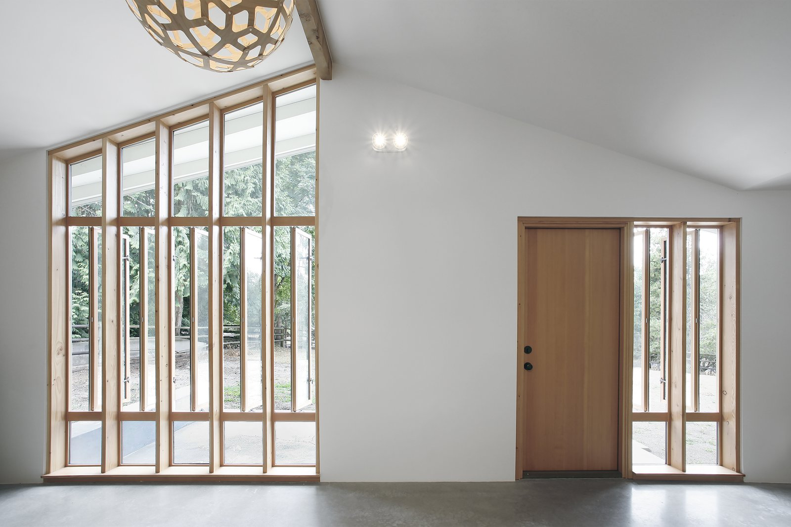 """""""The bank of full-height windows brings in tons of southern light, but it also gives the stable a strong street presence, and it ties into the stick-built window pattern already established at the entry to the main house,"""" Schaer says. The locally-sourced Douglas fir windows and doors were provided by Lindal Cedar Homes. Tagged: Doors, Swing Door Type, Wood, and Exterior.  Horse Stable Studio by Kelly Dawson"""