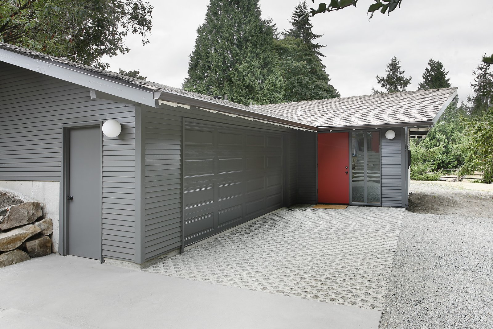 """""""The stable/garage was built with two intersecting gable roof forms,"""" Schaer says, which didn't match up with the inteiror spaces within. """"In order to provide a unified, singular main space, we dropped a flat ceiling at the entrance and linked it up with the main gable visible from the street.""""  Horse Stable Studio by Kelly Dawson"""