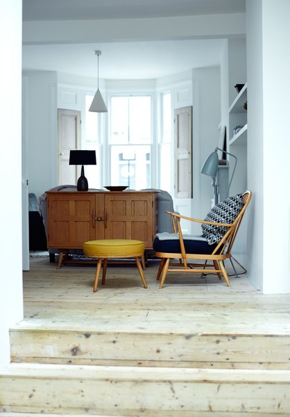 Furniture throughout the house echoes the soft materiality of the architectural details, which include original pine floorboards refinished with lye and wood soap. The music room armchair and footstool are vintage, from Ercol; the blue-gray Grasshopper floor lamp is by Greta Grossman from Gubi.