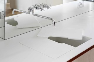8 Creative Ways to Let the Little Details Shine - Photo 5 of 8 - In a London flat designed by MWAI, the design team benefited from a collaborative relationship with their client, one of the owners of UK-based millwork and joinery company INTERIOR-iD, who produced many of the custom elements. Here, a custom-built Corian countertop and sink merge when the sink basin is covered by a removable cutting board that can be kept in place for an added work surface, or removed for dedicated sink use. The cutout in the center allows water from the tap to flow straight through to the custom Corian drainer.