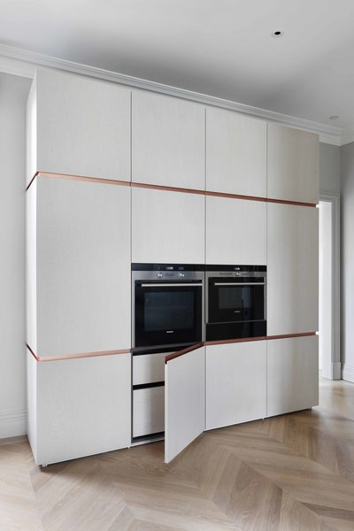 The opposite wall of the kitchen features built-in Siemens appliances and concealed storage. The custom INTERIOR-iD cabinets feature mitered doors, and brass trim, which passes fluidly around the edge of the doors, terminating at the back wall.