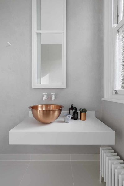 Metal details in the home transition to gradually darker tones as the spaces become increasingly private. In the guest bathroom, a solid brass bowl sink rests on top of a custom Corian base. White Dornbracht wall-mounted faucets sit below a custom mirror cabinet. In the bathroom and throughout the home, interior accents by Gunter & Co make elegant finishing touches.