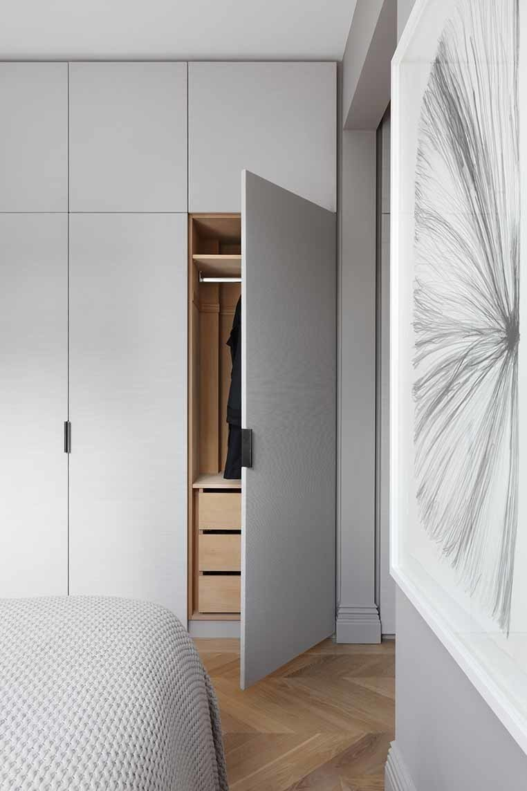 Fabric-clad wardrobe doors custom designed by INTERIOR-iD, along with Joseph Giles leather pulls, add texture to the master bedroom.  Storage by Dwell from Brass Is Everywhere at this Classical-Meets-Modern Flat in London