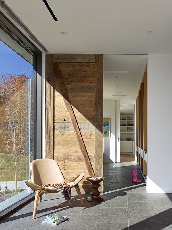 The front entry opens into a mud room. Each family member has their own cubby for storing shoes, coats, and backpacks. The wood sliding door, seen here, was built from reclaimed barn board. In front of it stands a Chair CH07 by Hans Wegner for Carl Hansen & Son Shell and Eames Walnut stool from Herman Miller.