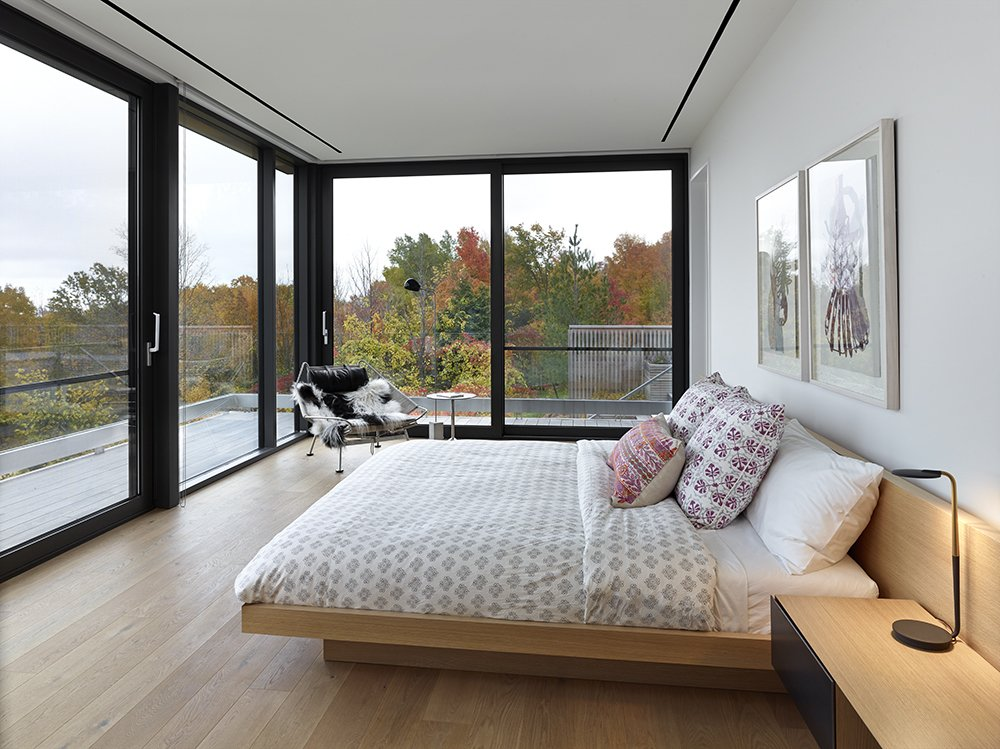 Natural light throughout the house eliminates the need for excessive overhead lighting. The master bedroom features a Pixo Optical LED table lamp, a Halyard chair by Hans Wegner for PP Møbler Flag, and David Weeks' Cement Standing floor lamp.  A Family Builds Their Dream Modern Home Overlooking the Georgian Bay by Caroline Wallis