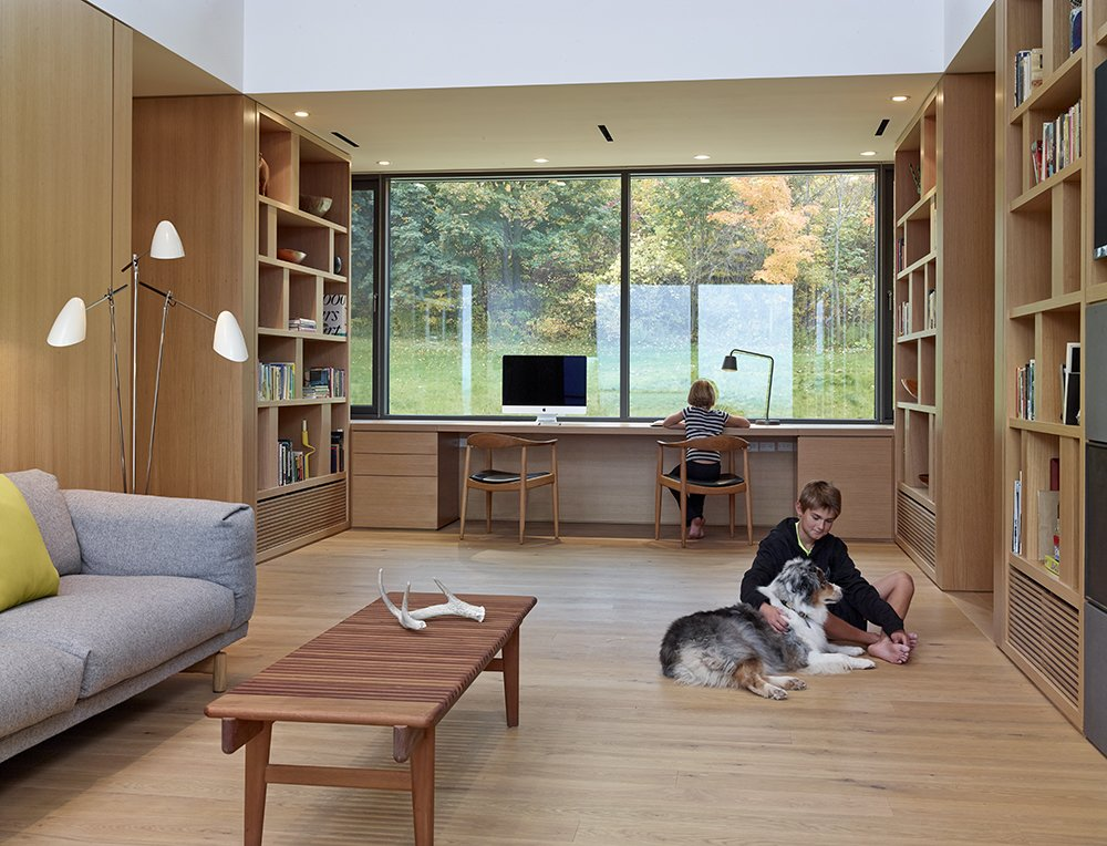 The lower submerged level is comprised of the kids' and guest bedrooms as well as the multi-purpose room—is a popular hangout for the kids and family dog, Roxy. The Chair and Bar Bench, both by Hans Wegner for PP Møbler, a Muuto 3-seater sofa by Andersen & Voll, and David Weeks' Tripod No. 303 floor lamp mix midcentury modern with contemporary design. Tagged: Office, Study, Library, Desk, Lamps, Chair, Storage, Bookcase, Shelves, and Medium Hardwood Floor.  A Family Builds Their Dream Modern Home Overlooking the Georgian Bay by Caroline Wallis
