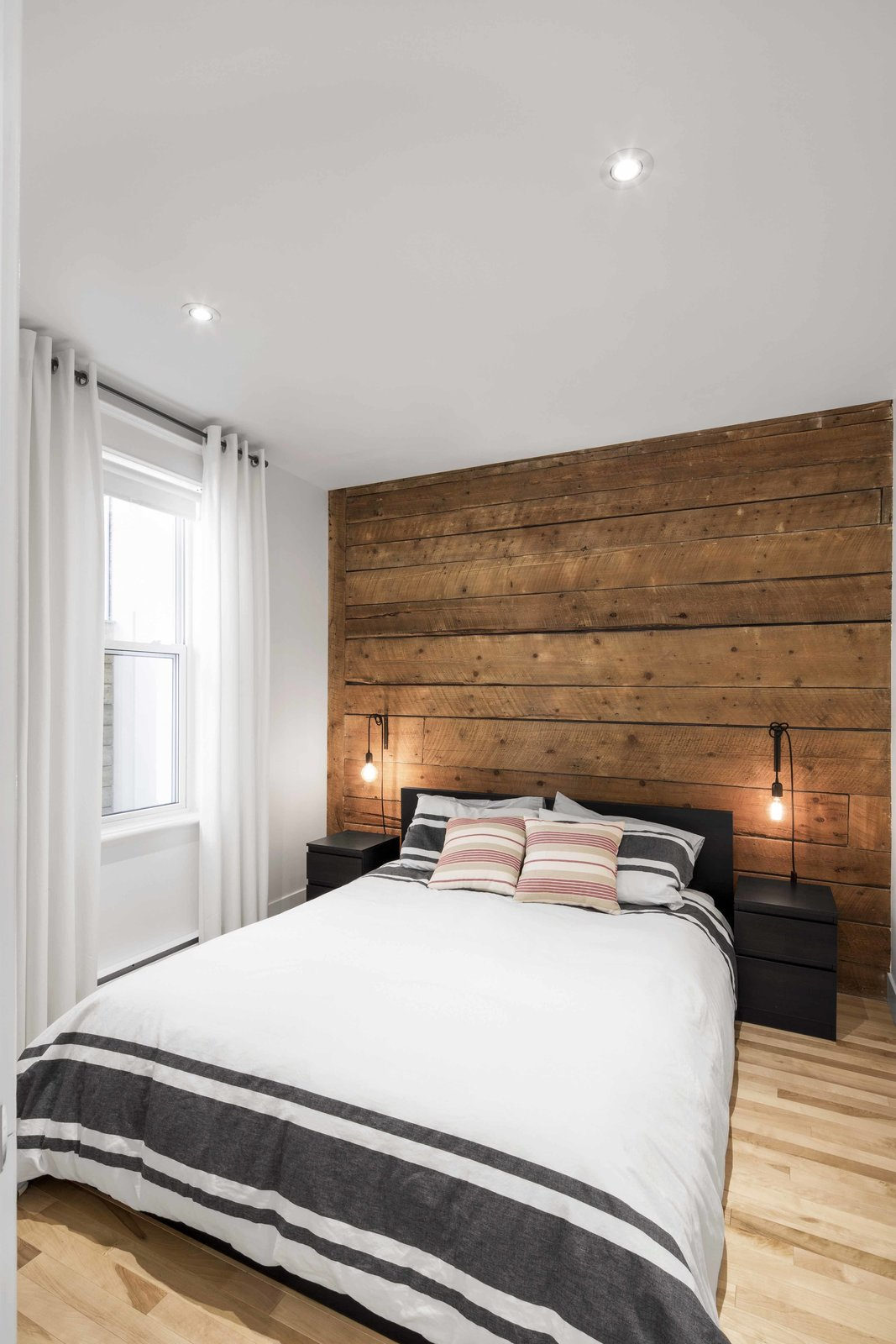 Exposed boards that were salvaged from the original apartment were installed into the master bedroom. They provide a rustic atmosphere, enhanced by the addition of DIY industrial lighting. The bedding, curtains, and bedside tables are all from IKEA.  Bedrooms by Dwell from Blocked in on Two Sides, a Renovation Opens a Quebec Apartment to Tons of Natural Light