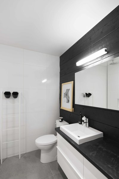The walls of the bathroom are covered in large, white ceramic tiles, with the exception of one side clad in reclaimed wood with an IKEA cabinet.