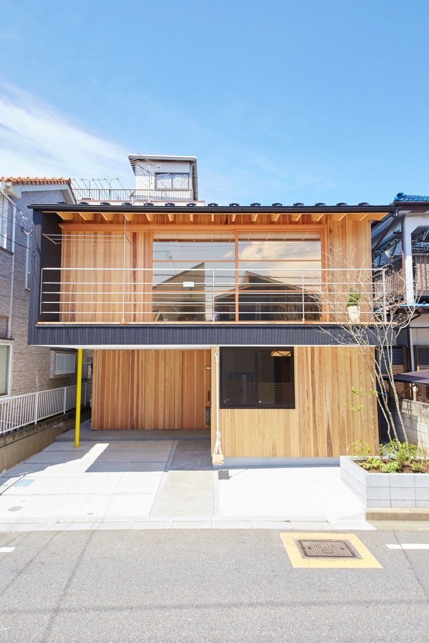 The house is surrounded by buildings on all sides except its south facade, which faces the street. An expansive operable window is key for effective ventilation during hot summer months. Additionally, a cantilevered balcony shelters a carport, bike storage, and even a playful swing. Tagged: Outdoor, Walkways, Front Yard, Small Patio, Porch, Deck, and Wood Patio, Porch, Deck.  Yanagisaki House by Caroline Wallis