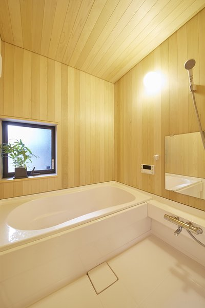 Modern home with bath room, drop in tub, open shower, and wall lighting. The bathroom's sauna-like interior includes a deep Toto bathtub—characteristic of traditional Japanese baths. The wooden hiba paneling, chosen because it is more water resistant than hinoki, is specific to the Northern Aomori region of Japan. Photo 6 of Yanagisaki House