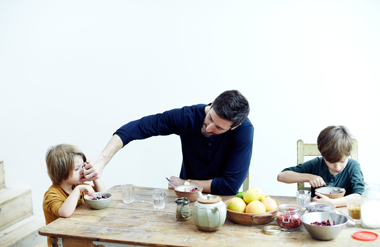 In the Norton family home in London's Stoke Newington district, Jamie Norton and his sons, Miller, 3, and Ned, 7, enjoy a meal at a salvaged table and chairs found at a local vintage shop. The ceramics are by Richard Batterham.  Photo 1 of 9 in This Kitchen Is as Cozy as Your Favorite Coffee Shop and That's Exactly the Idea