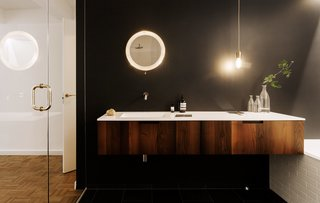 We Can't Get Enough of This German Apartment's Sleek Matte-Black Kitchen - Photo 5 of 11 - A glass wall separates the master bathroom from the bedroom, a design movethe couple had seen in hotels. A Universal vanity in acacia wood from Boffi was chosen to add some warmth, along with a stone floor with radiant heating. The mirror is a vintage design by Mathieu Matégot.