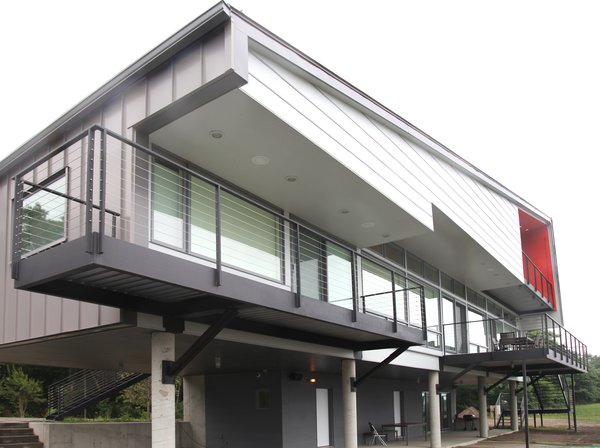"""""""A majority of the house is lifted on concrete columns to maximize the views and also provide a covered ground plane for protected parking and outdoor living,"""" Mulvena says. """"Future additions to the house can be built on this ground level within the existing structure."""" Photo 2 of Hudson Valley Dream Retreat modern home"""