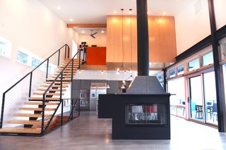 The fireplace, which sits on buffed concrete flooring at the center of the ground floor, was custom-made by Mapos.