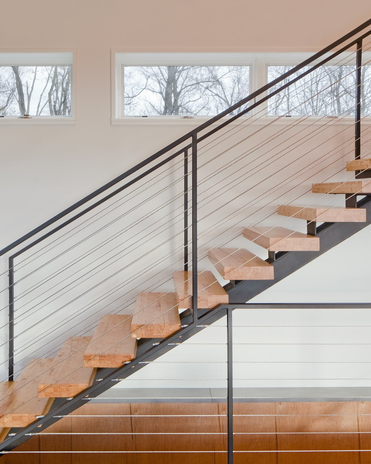 """The clients desired a maintenance-free, year-round home using the ultimate in 'green' building methodologies,"" Mulvena says. The staircase is an example of the construction's mindset: it is made from the leftover laminated veneer lumber used on the roof. Tagged: Staircase, Metal Railing, and Wood Tread.  Hudson Valley Dream Retreat by Kelly Dawson"