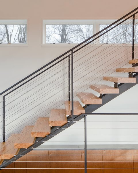"""The clients desired a maintenance-free, year-round home using the ultimate in 'green' building methodologies,"" Mulvena says. The staircase is an example of the construction's mindset: it is made from the leftover laminated veneer lumber used on the roof. Photo 6 of Hudson Valley Dream Retreat modern home"