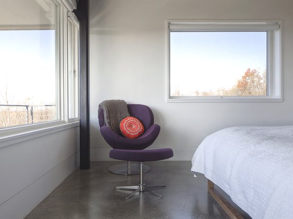 """The [owner] is a self-proclaimed minimalist who desired concrete throughout as a backdrop to her furniture, and eventually, her artwork,"" Mulvena says. The Schelly chair and ottoman in the master bedroom are by BoConcept. Photo 7 of Hudson Valley Dream Retreat modern home"