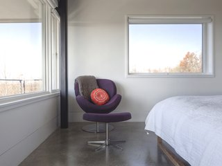 """The [owner] is a self-proclaimed minimalist who desired concrete throughout as a backdrop to her furniture, and eventually, her artwork,"" Mulvena says. The Schelly chair and ottoman in the master bedroom are by BoConcept."