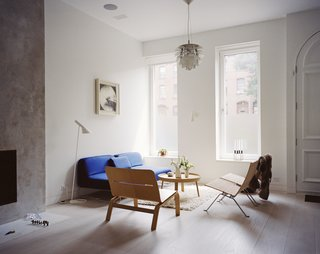 Our Scandinavian Style Dreams Come True in This Brooklyn Town House - Photo 5 of 9 - The living room is furnished with rattan chairs from Fritz Hansen, a Muuto side table, an Artichoke pendant by Poul Henningsen for Louis Poulsen, and a blue Living Divani sofa, one of a few color-popping accents found throughout.