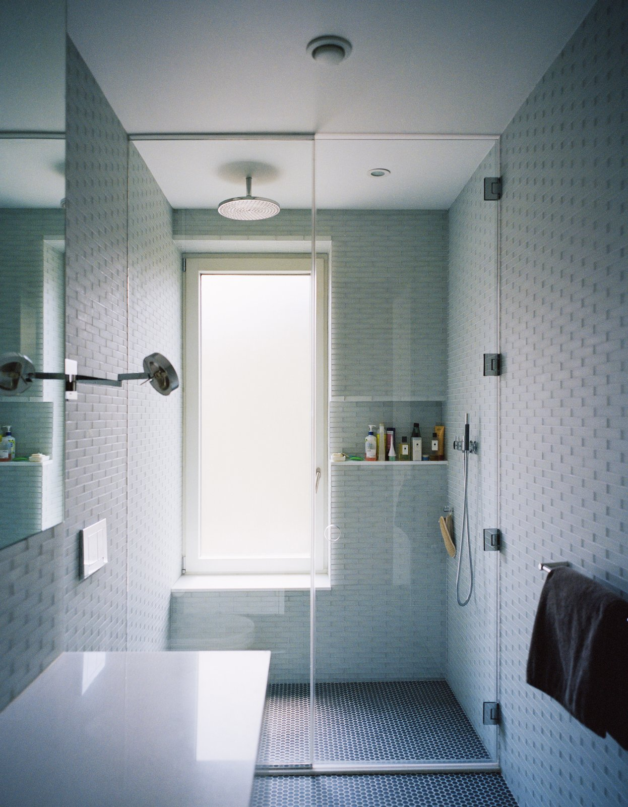 Triple-glazed, frosted windows emit soft, filtered light against pale gray and blue surfaces inthe master bathroom. Lucian Field matte-glass and Lucian Mosaics penny round tiles, both by Ann Sacks, line the floor and walls. Tagged: Bath Room, Open Shower, Recessed Lighting, and Ceiling Lighting.  Photo 4 of 10 in Our Scandinavian Style Dreams Come True in This Brooklyn Town House