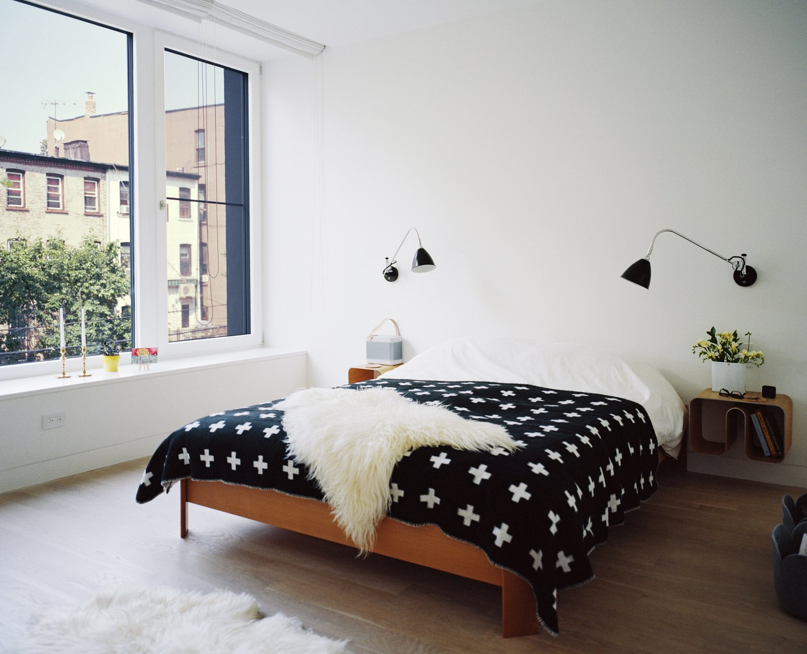 Set atop a BoConcept bed, a graphic blanket by Pia Wallén for HAY punctuates the master bedroom. The sconces are by Robert Dudley Best for Bestlite. Tagged: Bedroom, Bed, Light Hardwood Floor, and Wall Lighting.  Bedrooms by Dwell from Our Scandinavian Style Dreams Come True in This Brooklyn Town House